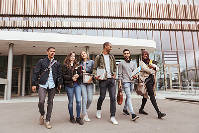 Full length of multi-ethnic university students walking against building in campus - p426m2072279 by Kentaroo Tryman