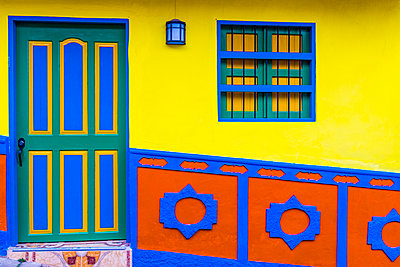 The facade of a colourful building covered in traditional local tiles, in the picturesque town of Guatape, Colombia - p871m2032221 by Chris Mouyiaris