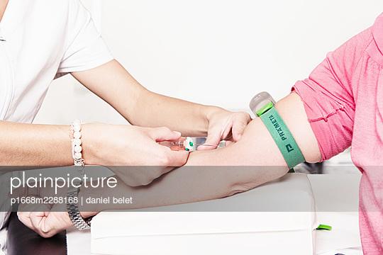Patient receives an intravenous syringe - p1668m2288168 by daniel belet