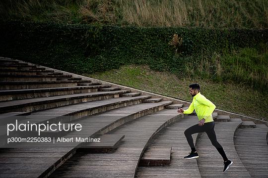 Male athlete running on steps at park - p300m2250383 by Albert Martínez