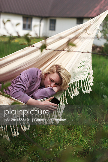 Woman using phone in hammock - p312m1533101 by Christina Strehlow