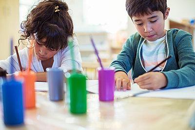 Students painting in classroom - p1023m1146444 by Paul Bradbury