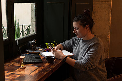 Young woman looks at her phone while studying in a retro pub - p1166m2189763 by Cavan Images