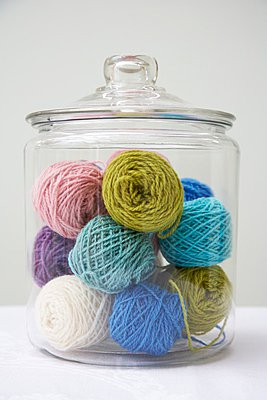Balls of wool of various colours in glass jar - p1183m997652 by Murphy, Charlotte