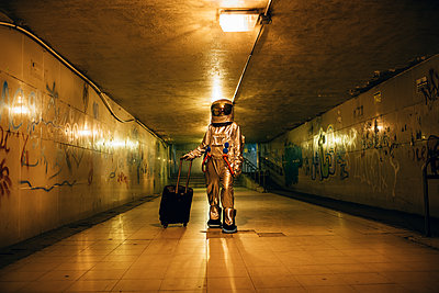 Spaceman in the city at night in underpass with rolling suitcase - p300m2043192 by Vasily Pindyurin