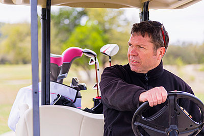 Mature man riding cart on golf course - p300m798048f by André Babiak