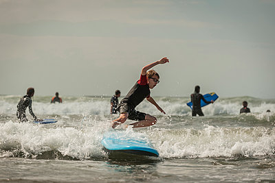 Boy surfboarding - p300m981546f by Andreas Pacek