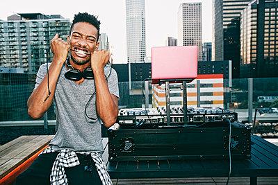 Black DJ biting headphones cord on urban rooftop - p555m1301708 by Peathegee Inc