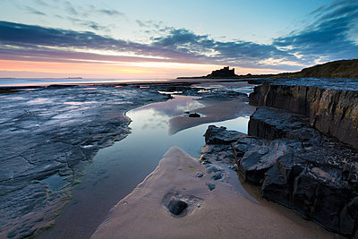 View towards Bamburgh Castle at sunrise from Bamburgh Beach, Bamburgh, Northumberland, England, United Kingdom, Europe - p871m1498194 by Lee Frost