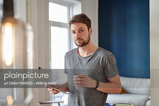 Junger Mann mit Tablet Computer und Kaffeebecher - p1124m1589453 von Willing-Holtz