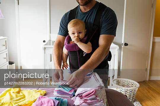 Mid adult man doing chores with baby daughter in baby sling - p1427m2283202 by Roberto Westbrook
