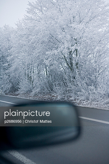Rückspiegel eines Autos vor Winterlandschaft - p2686956 von Christof Mattes