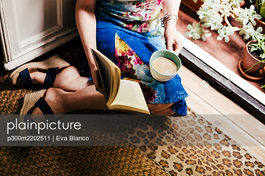 Woman holding coffee cup and book while sitting on floor at home - p300m2202511 by Eva Blanco