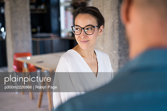 Businesswoman looking away while standing with man at office - p300m2226966 by Robijn Page