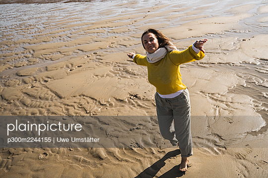 Carefree woman dancing at beach during sunny day - p300m2244155 by Uwe Umstätter
