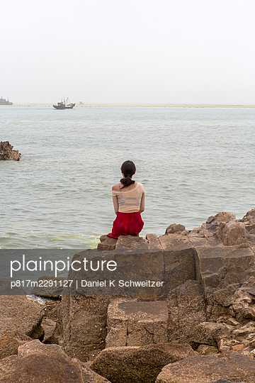Young woman looking at sea, rear view - p817m2291127 by Daniel K Schweitzer