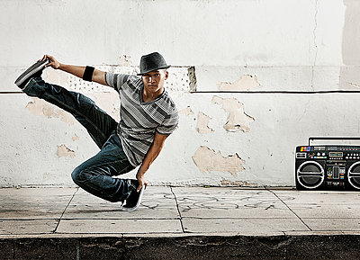 A young man breakdancing, balancing on one foot with his leg outstretched.  - p1100m1107162 by Mint Images