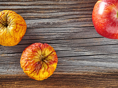 Fresh red apple and a shrivelled one on rough wood - p300m1081346f by Dieter Schewig