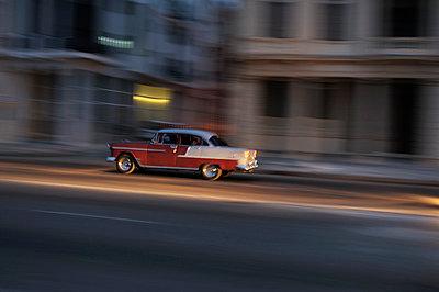 Cuba, Havana, American vintage car driving on a road at twilight - p300m1121134 by Stefan Espenhahn