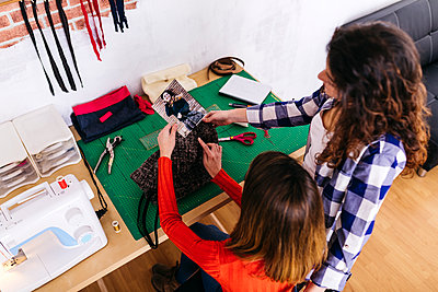 Two fashion designers in studio looking at photography - p300m1568101 by Josep Rovirosa