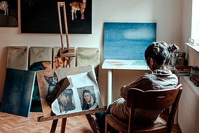 Rear view of a female artist sitting in her studio in front of a painting - p300m2132324 by Oxana Guryanova