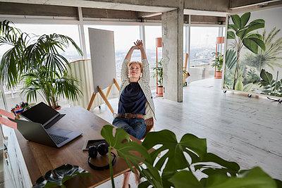Female entrepreneur relaxing while sitting at desk in office - p300m2265232 by Jo Kirchherr