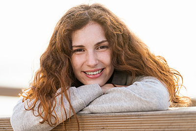 Beautiful smiling woman with arms crossed leaning on railing - p300m2286961 by Steve Brookland