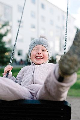 Boy having fun on swing in playground - p312m1131293f by Malin Morner
