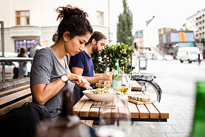Side view of man and woman having lunch at sidewalk cafe in city - p426m1212823 by Maskot