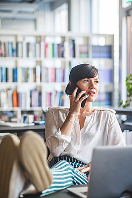 Creative businesswoman talking on mobile phone while relaxing at desk in office - p426m2032741 by Maskot