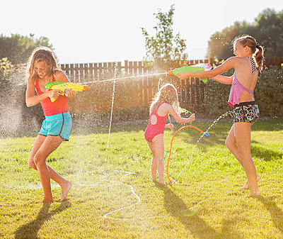 Caucasian girls shooting water guns - p555m1479002 by Mike Kemp