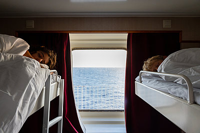 Zwei Kinder schlafen in der Koje, Blick aufs Meer - p756m2295406 von Bénédicte Lassalle