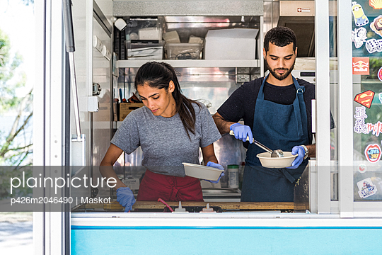 Confident young multi-ethnic male and female colleagues working in food truck - p426m2046490 by Maskot