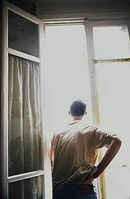 Man looking outside a window - p1028m2176260 by Jean Marmeisse