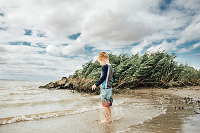 Side view of boy standing at beach against cloudy sky - p1166m2001064 by Cavan Images