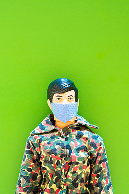 A toy soldier doll wearing a camouflage jacket and surgical face mask - p1302m2181356 by Richard Nixon