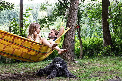 Father and daughter in a hammock - p294m2206273 by Paolo