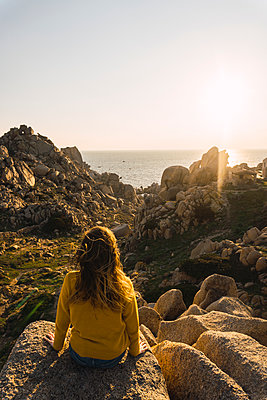 Italy, Sardinia, woman on a hiking trip sitting on rock at the coast - p300m1580926 by Kike Arnaiz