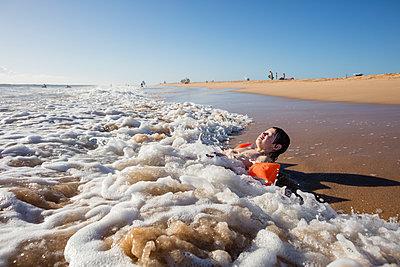 Boy lying on beach - p312m1164842 by Plattform photography