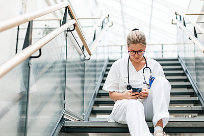 Female doctor sitting on stairs - p312m2174372 by Scandinav
