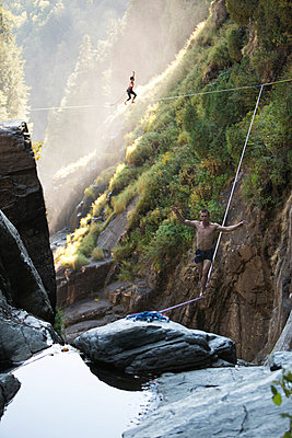 Male & female highliners simultaneously walking a two-way highline - p343m874112f by Jared Alden
