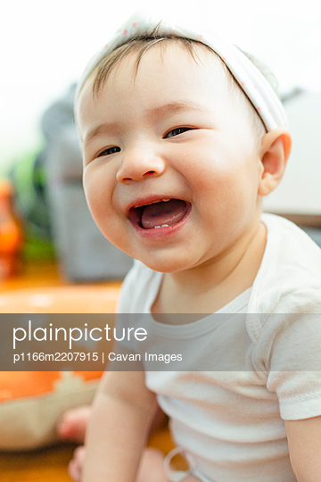 Close-up portrait of adorable Asian baby girl smiling at camera - p1166m2207915 by Cavan Images