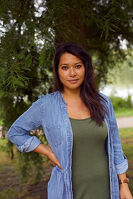Portrait of dark-haired woman in a park - p1491m2176033 by Jessica Prautzsch