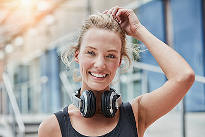 Portrait of smiling young woman with headphones - p300m2084034 by Roger Richter