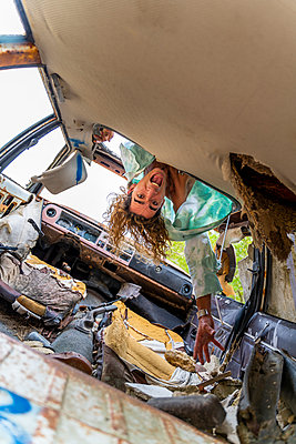 Young blond man in junk car, upside down - p300m2160026 by VITTA GALLERY