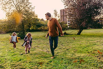 Father running with daughters on a meadow in autumn - p300m2160617 by Mareen Fischinger
