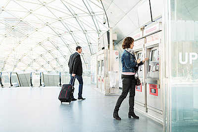 Businesswoman buying ticket while colleague walking at railroad station - p426m1085316f by Kentaroo Tryman