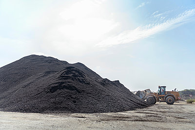 Digger with large pile of recycled soil in concrete recycling site - p429m2019318 by Monty Rakusen