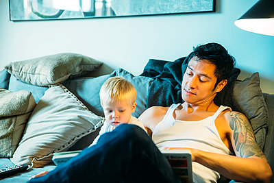 Father and son reading on sofa in living room - p555m1411002 by Inti St Clair photography