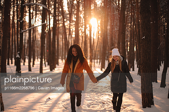 Happy girlfriends holding hands while walking in snow covered park - p1166m2268796 by Cavan Images